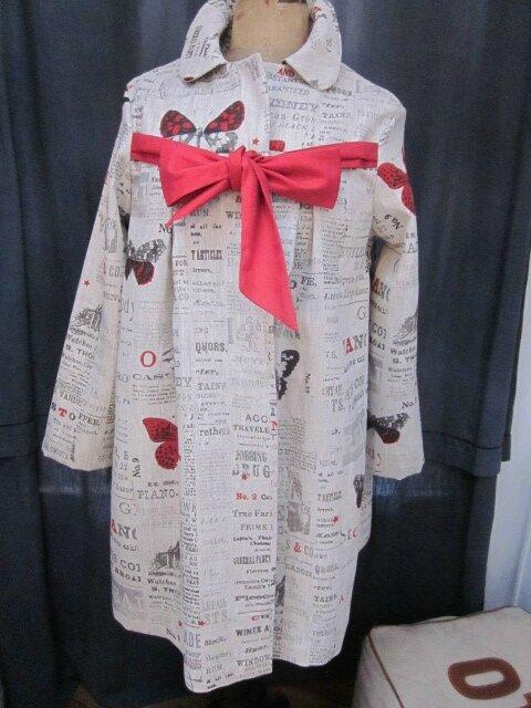 Un manteau AGLAE en lin brut imprimé papillons rouge sur fond de journal fermé par un noeud de lin rouge