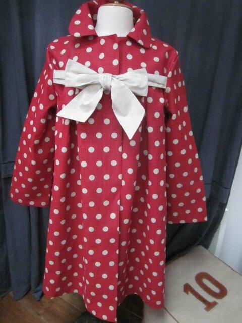 Un manteau AGLAE en lin rouge à pois ficelle fermé par un noeud de lin brut...