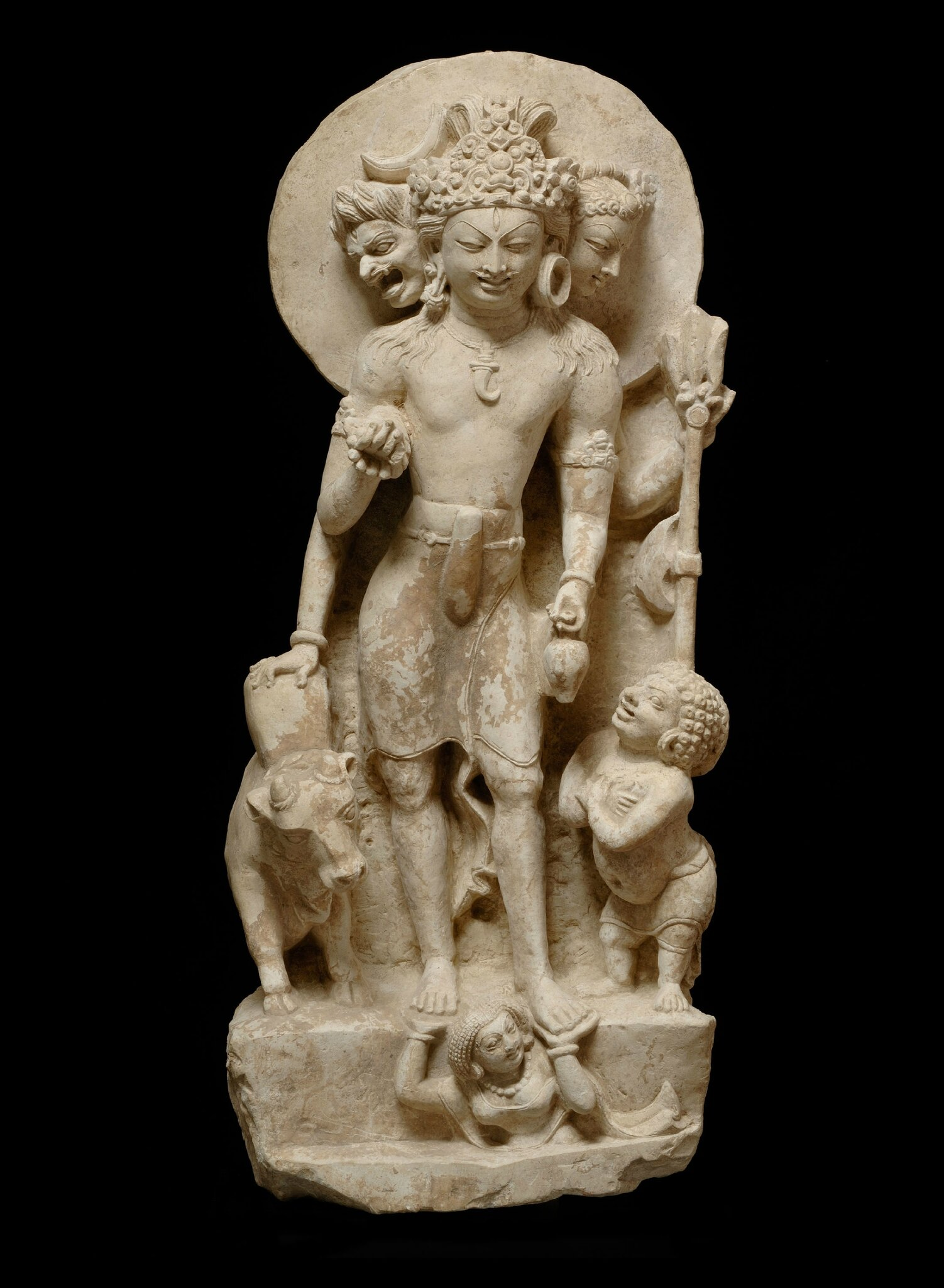 Three_headed_Shiva_with_Nandi_Prithvi_and_a_gana-North-west_India-Punjab-Salt_Hills-7th_8th_C-limestone-ht_58cmJohn_Eskenazi