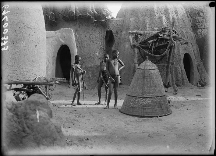 Enfants devant une grande nasse au milieu des cases en pisé