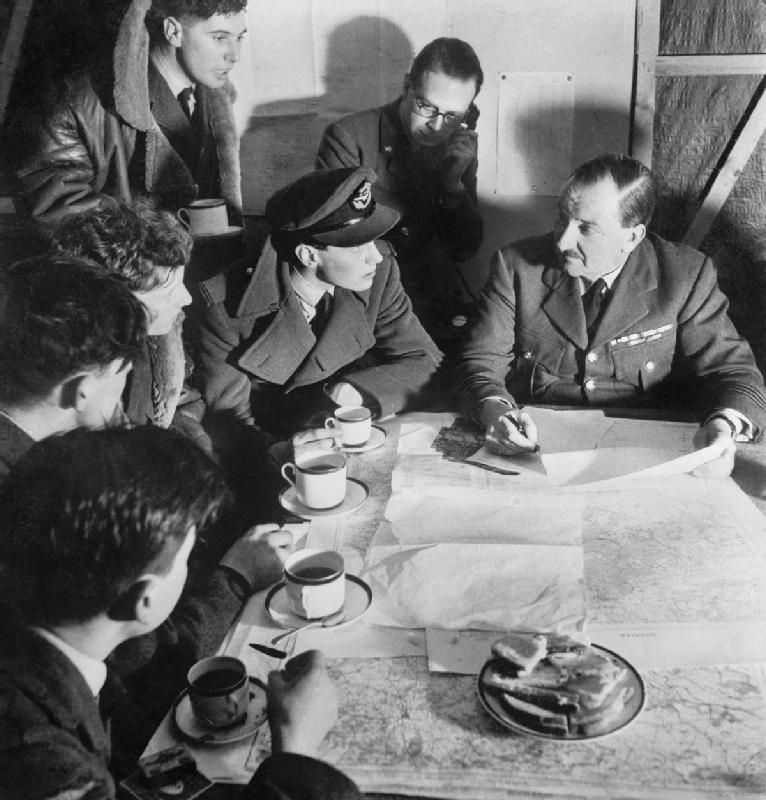 Cecil Beaton photograph of an RAF bomber crew being debriefed by the squadron intellgence officer on their return from a night raid over Germany, 1941