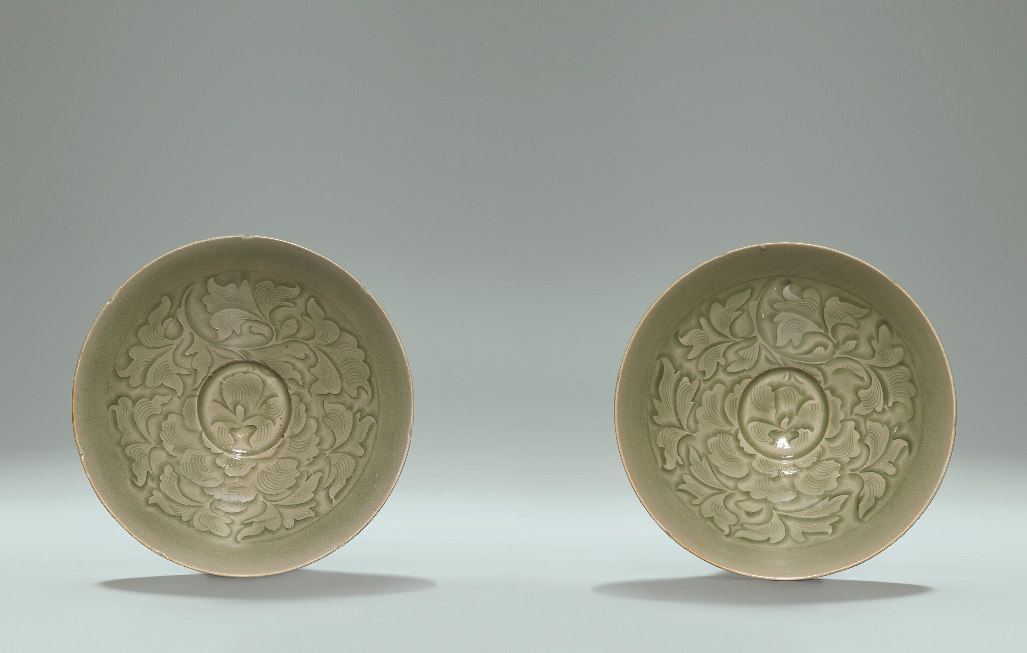 Two rare and superbly carved Yaozhou celadon shallow bowls, Northern Song Dynasty, 11th century