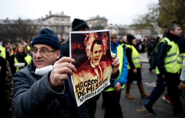 640x410_a-demonstrator-holds-a-placard-displaying-a-picture-a-french-president-emmanuel-macron-with-the