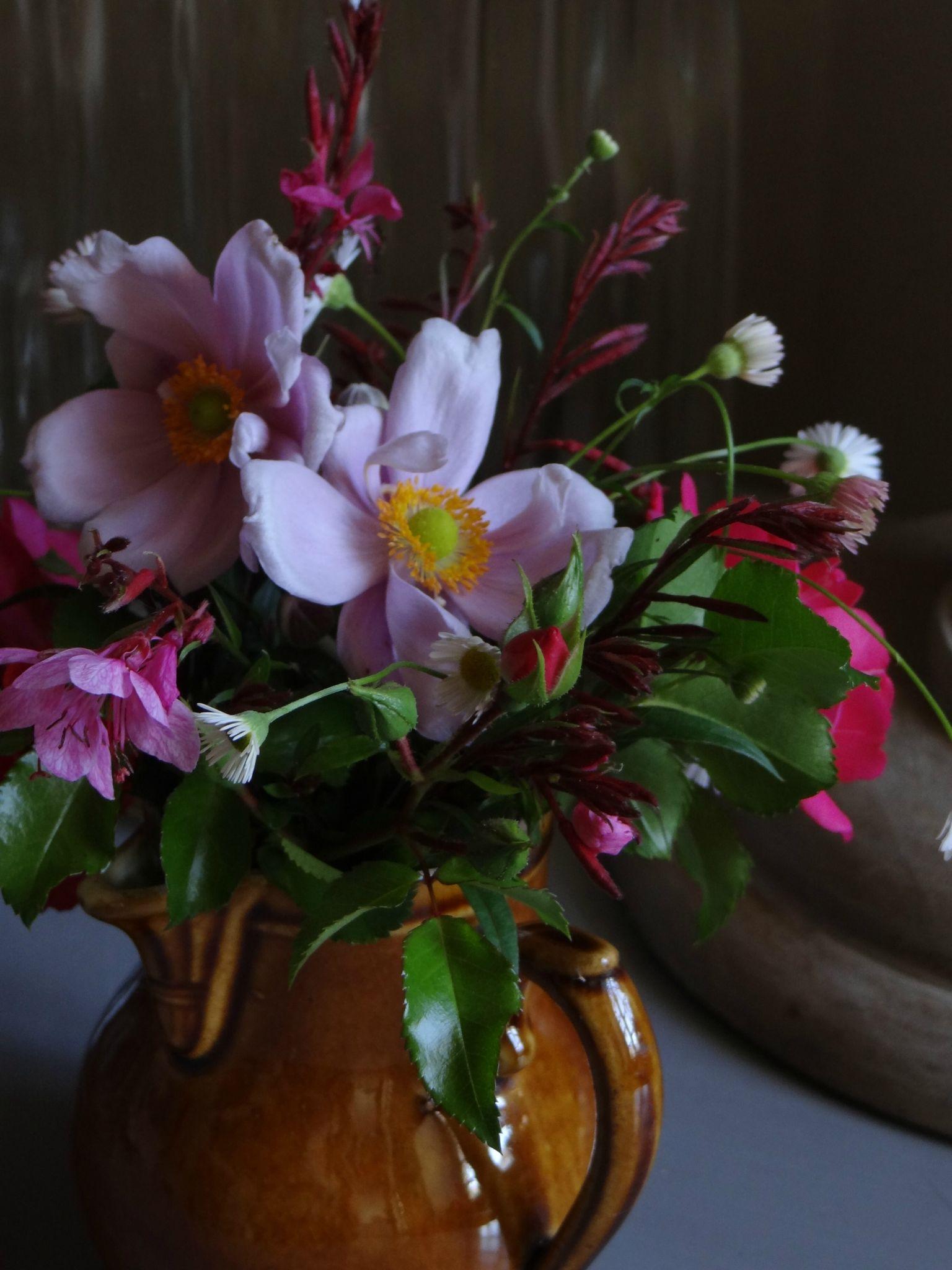 Bouquet échevelé du jardin dans un tout petit pot en grès