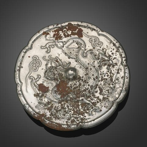 A silvery bronze eight-lobed mirror with dragon decoration, Tang dynasty.