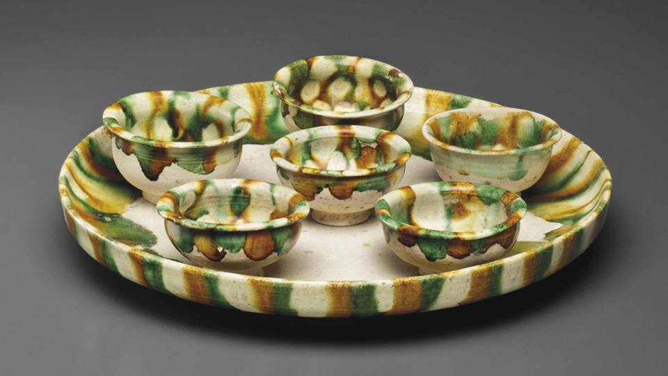 A sancai-glazed pottery circular tray and six cups, Tang dynasty (AD 618-907)