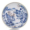 A fine and rare underglaze blue and copper red decorated deep porcelain plate in the style of the 'master of the rocks'.