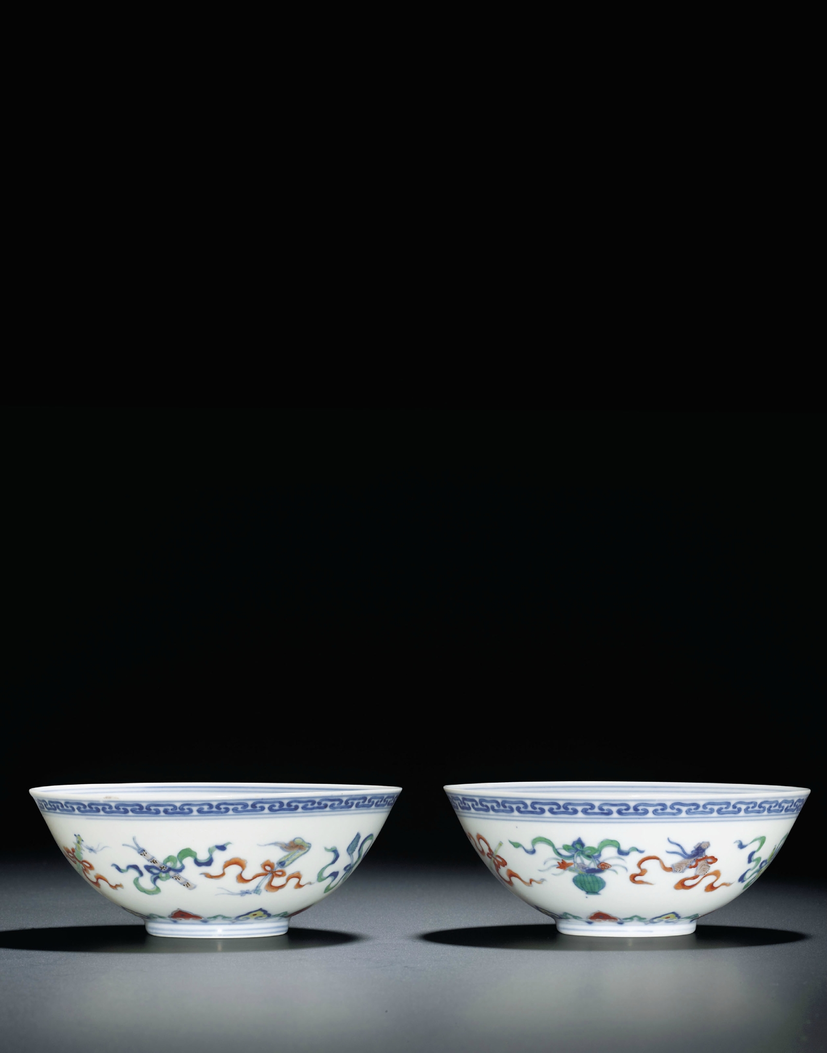 A fine pair of doucai 'Daoist emblems' bowls, Yongzheng six-character marks within double circles and of the period (1723-1735)