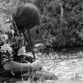 Une femme se tresse les cheveux au bord de la riviere
