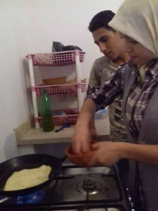 Farah veille à la cuisson sous l'oeil de Farid