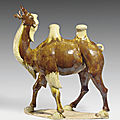 A massive well-modeled chestnut and cream-glazed pottery figure of a Bactrian camel, Tang dynasty (618-907)