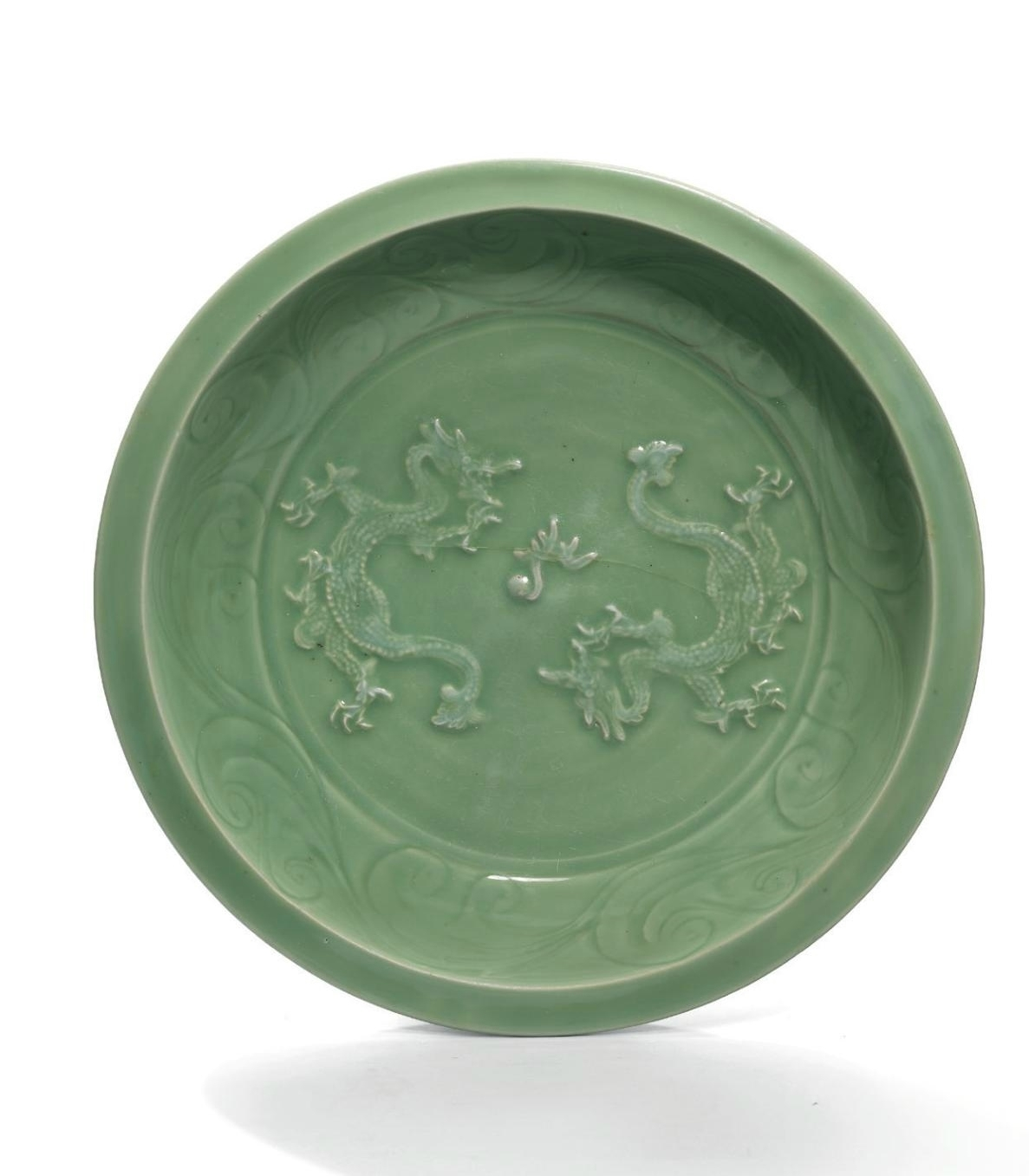 A very rare large carved and moulded 'double-dragon' Longquan celadon charger, Yuan dynasty (1279-1368)