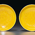 A pair of small yellow-glazed incised dishes, kangxi six-character marks and of the period (1662-1722)