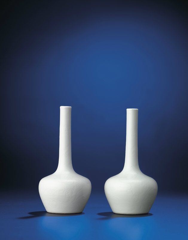 A fine pair of very rare small incised white-glazed bottle vases, Yongzheng six-character marks within double circles and of the period (1723-1735)