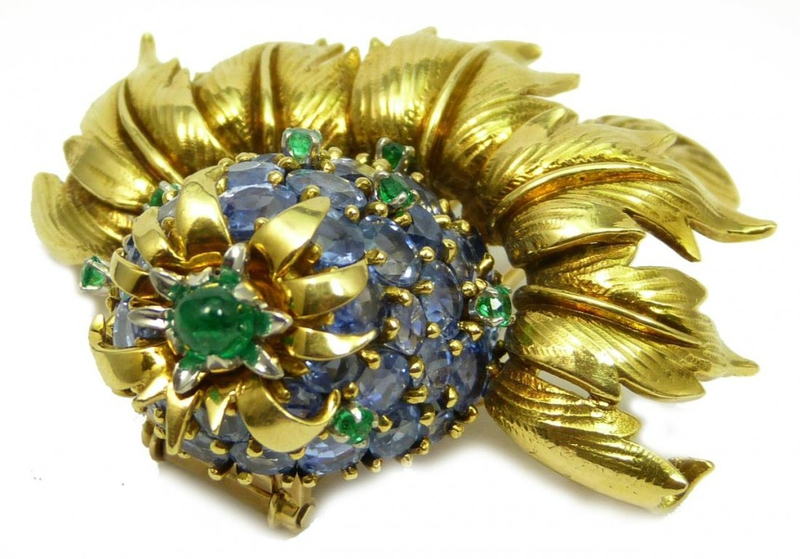 Schlumberger Tiffany & Company 18K yellow gold floral brooch pendant featuring round cut attractive light blue sapphires accented with 7 round cut emeralds and topped with a round cabochon emerald