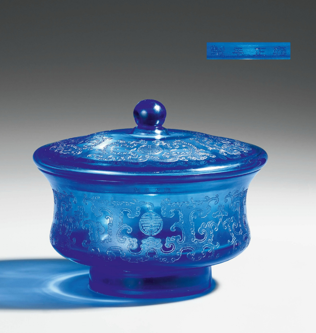 A transparent blue glass footed bowl with matching lid