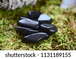 stock-photo-tumbled-apache-tears-obsidian-apache-tears-crystal-volcanic-black-obsidian-grounding-protection-1131189155
